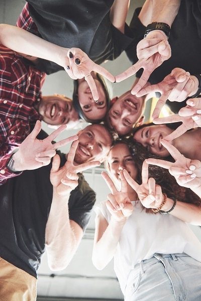 Happy group of friends with their hands together in the middle